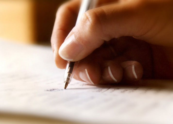 Close-up photo of a hand holding a pen and writing on paper